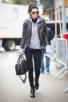 Chica usando hoddies y blazer en color negro y gris mientras camina por la calle