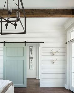 Cottage bedroom boasts a white shiplap wall fitted with a blue shiplap barn door on rails illuminated by an iron lantern.