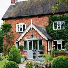 red brick farmhouse with large central porch, white coving and light blue front…