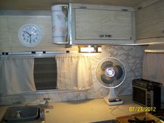 This is how the kitchen looks now with new curtains and clock. Vintage 1969 Shasta travel trailer.