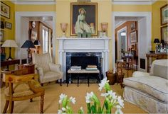 Yellow-Gil Schafer Greek revival living room: sisal rug, great furniture placement, peeking into a pumpkin/terra-cotta dining room; Miles Redd design.