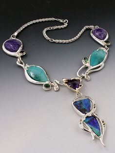 Courtney  developed an ethereal color palette using purple sodalite, custom cut blue-green chrysocollas with malachite specs, and dazzling green tourmaline set in 14k yellow gold bezels throughout the piece. The center stone is a cushion cut purple amethyst set in 14k yellow gold with two brilliant Australian opals hanging down. The necklace it set in platinum silver with 14k yellow gold bead accents. Premier Jewelry, Blue Green, Yellow, Australian Opal, Green Tourmaline, Opals, Purple Amethyst, Cushion Cut, Gold Beads