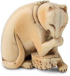 Unsigned ivory netsuke,18th C., cat. Seated on its haunches, it secures an upturned awabi shell while licking its right paw.