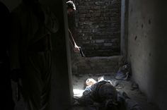 An Afghan resident points his weapon at the dead body of an unidentified militant, as a way of showing his hatred for insurgents, at a building where three other militants were located at, after an attack in Kabul, July 17, 2014. REUTERS/Omar Sobhani