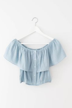 Light blue off shoulder crop top with button detailing in front. Stretchy and elasticated waistline. Lightweight non-stretch woven material. 77% Rayon 23% Nylo