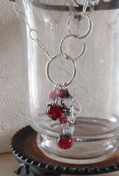 Merlot Circle Necklace. Rich ruby colored handmade glass beads and semi precious gems in a unique asymmetrical design by Donna Sauers Designs. Perfect color for the holidays and all year!