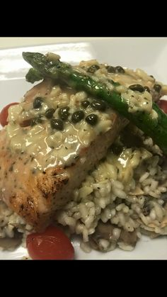 Grilled wild salmon topped with a lemon, butter chardonnay sauce with capers over wild mushroom risotto.
