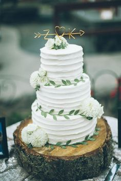 Three tiered cake wrapped with greenery on a tree trunk platter | Image by From The Daisies