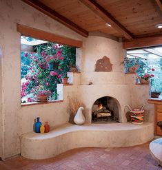 The interior of the old garage was finished with wallboard, a ceiling fan, downlights, and a brick floor. The corner contains a Southwestern-style fireplace, complete with a curvy hearth for sitting and a tiered mantel.