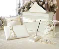 "This ivory satin wedding set includes six wedding accessories essential to completing your perfect day.  Included are the following items:  one 10"" x 6.5"" guest book, one 3.25"" x 5.25"" pen set, one 7.5"" ring pillow, one 7.5"" flower basket and one garter -- all of which are packaged to fit inside the 13.5"" x 7"" x 8.5"" card box.  Most of the accessories (excluding the pillow and basket) are accented by a silver rhinestone ornament.  The silver pen contains black ink.  Also available in white."