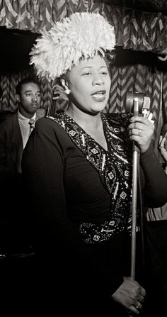 An awestruck Dizzy Gillespie watching Ella Fitzgerald sing at the Downbeat Club in New York City, 1947. Jazz legend, Milt Jackson in the background to the left. Photo by William P. Gottlieb.