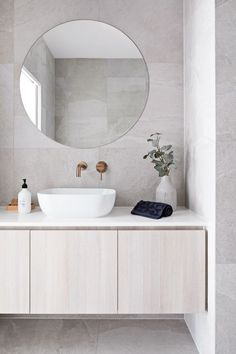 Clean lines and large format grey tile covers the floor and walls. A round frameless mirror hangs over a white sink with brass wall mounted bathroom sink faucet. The flat paneled vanity is wall mounted and has a thin white countertop Bathroom Renos, Bathroom Renovations, Decorating Bathrooms, Bathroom Ideas, Bathroom Cabinets, Restroom Cabinets, Bathroom Pictures, Bathroom Inspo, Budget Bathroom