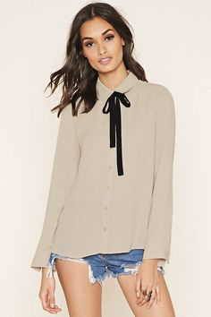 A woven shirt with button-cuff long sleeves, a basic collar, a button-up front, and a removable contrast self-tie sash at the neck.