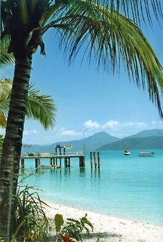 Fitzroy Island is a tropical island, off de coast from Cairns, Queensland_ East Australia. De Australian mainland can be seen in de background. De sign on de pier says 'Private Jetty - no fishing'. De resorts glass bottomed boat is available for guests n can be seen at right.