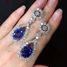 A dazzling masterpiece! A pair of 13 carats each Oval Shape unheated Burmese Sapphire dangling earrings, surrounded by 10 carats of sparkling round diamonds (333612)