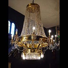 Opulent twelve branched gilt brass and crystal chandelier in the English Regency manner. The main rim with smaller lower rim is applied with candle branches and strung with glass beads and pendants. The brass structure is decorated with rosette squares and round paterae.