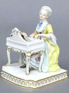 Meissen Model: E 1        Description: The Senses - Hearing   Modeled By: Johann Carl Schoenheit ca. 1772   Mark: E 1       Painter Number: 49 - Julius Goetze    Height: 4.9 in - 12.5 cm  Notes: Yellow Dress