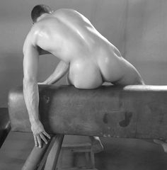 Nude male model on a pommel horse. I know it's not a real horse but it does have 4 legs