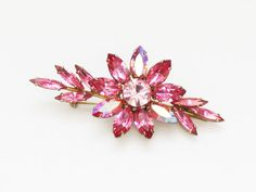 Era: circa 1950s  Label/Designer: Regency  Measurements: 3 inches x 1.5 inches  Materials: pink rhinestones, gold tone metal  Condition: excellent  Description: An ultra feminine pink flower brooch by Regency. No notable flaws.