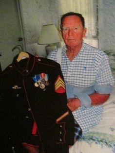 """Sgt. Jim Foster of Blue Heron Pines mobile home park holds his Marin dress uniform. He is a member of """"The Chosin Few,"""" who fought with the 1st Marine Division in Korea. Sun photo by Don Moore"""