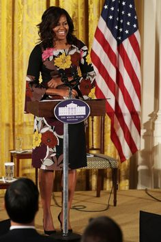 First Lady Michelle Obama. FLOTUS wears a warm floral tea-length dress with bell sleeves and black pointed-toe pumps while addressing Veterans' homelessness in the White House.