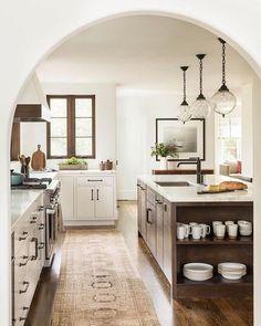 White kitchen with warm wood and glass globe pendants