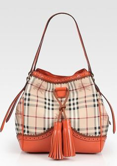 This Small Tote Bag has a scalloped tangerine trim with two large tassels front and center. This bag will definitely fit in with the pretty pumpkin and brown shades of the fall season.  Burberry, $1200.00