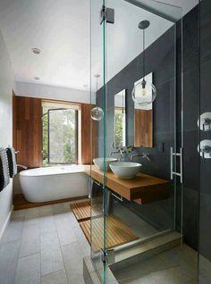 Banheira de louça, box separado. Bom uso da madeira e da cor cinza.