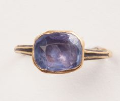 A gold 17th- century ring with a a natural, oval, faceted color- changing sapphire (app. 3 carats) ranging from bright sky blue to dreamy rose pink. The shank is decorated with black and white enamel, European.