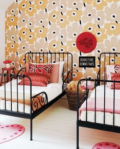 Sophisticated Kids' Room - A Marimekko-inspired accent wall creates an adorable backdrop for this darling girls' room. The addition of several accent pillows in complementary patterns, a dash of word art, and charming heart-shaped pillows give the room a layered feel.