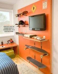 12 - In this contemporary room,an accent wall is painted in bright orange for happiness and a warm feel. The skateboard shelves are quite interesting and add a sporty, extrovert and uninhibited look which suits the personality of the sports lover boy. Skateboard Shelves, Boys Skateboard Room, Skateboard Furniture, Teenage Room, Boys Room Decor, Bedroom Decor, Kids Room, Wall Decor, Cool Boys Room