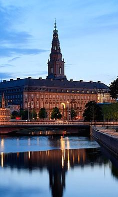 Christiansborg Castle and tower as seen across Slotsholmen Canal at twilight. Copenhagen, Denmark