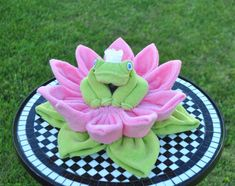 Baby Washcloth Water Lily. WashAgami ™. This is a great complement to the Washcloth Frog (not included) You can attach it to your diaper cake, attach it to the top of your gift package or simply use it alone as a centerpiece. I comes with two templates, one for the Lily Pad Base (pic 1) and one for the Lily Petal Base (pic 2).  This 56:00 minute, easy to follow, video tutorial will walk you through the simple process of creating this darling Water Lily made from baby washcloths. ** Frog is…