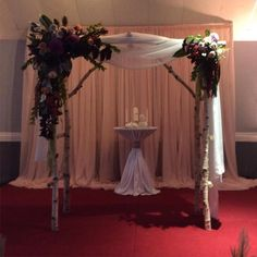 Birchwood ceremony arbor with fresh floral and draping.