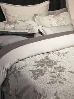 A sumptuous pattern of beautifully rendered silver peonies shimmering on a textured grey ground.  Via our storefront's selection of linens & bedding.