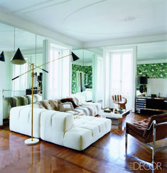 13 Mid-Century Modern Living Rooms for Inspiration - Some affordable, some luxury living rooms, but all in a beautiful style with mid-century furniture, mid-century decoration, and great taste! If you're looking for ideas, click here to find some! A mid-century theme living room with a mirror wall to make it look much bigger. Stylish mid-century lamps and furniture.