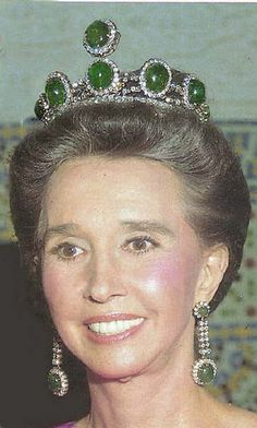 a close up of Aline wearing the emeralds as a tiara, with matching ear pendants