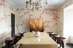 The dining room of a London home by Rafael de Cárdenas features bespoke de Gournay wallpaper, a Maison Charles Bubble chandelier, a Karl Springer table of lacquered goat skin from Talisman and Hollywood Klismos chairs by Grosfeld House from High Style Deco.