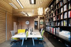 Home Office:Wood Paneled Walls Polished Concrete Floor Complex Elegant Interior Design Black Wooden Bookshelves Fluorescent Light Tubes Wooden Ceiling Modern Yellow Desk Chair Long Home Office Desk Modern Office Desk Fla Formal Factory Redesign Into a Many Coloured Office and Workspace