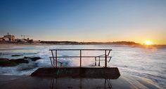 Sunrise on Bondi Beach in Sydney, Australia with a handrail in foreground