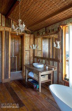 A fim de reforçar o estilo rústico, uma antiga mesa de fazenda serve de bancada no banheiro, cujo piso é de cimento queimado apenas na área do boxe.