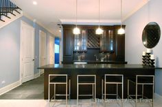gray slate floors, espresso brown stained cabinets and bar with black granite countertops, modern chrome stools with black leather cushions seats, glass pendant island lights, glass front cabinets and wine rack. brown espresso blue gray basement wet bar colors.