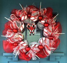 """- Wire wreath frame covered with red and white mesh intertwined with """"candy cane"""" (red & white stripped) mesh. - Shiny, glitter and matte red ornaments along with shimmery white and red icicles sticki"""