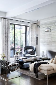 loving the Lisa chair, marbelized wall + floor-to-ceiling industrial windows