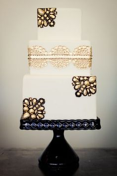 Black & Gold Cake. Stun-ing! Great contrast. Love the square angles for the cake, and that the jewel embellishment come in from the sites. Layers balanced and symmetrical without being identical.
