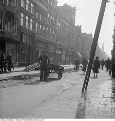 1944 - 1945. View of the Haarlemmerstraat in Amsterdam. The Haarlemmerstraat is a busy shopping street that extends from the Nieuwendijk in western direction between Singel to the Korte Prinsengracht. From there, up to the Haarlemmerplein, the street is called the Haarlemmerdijk. Photo Nederlands Fotomuseum / Cas Oorthuys. #amsterdam #worldwar2 #Haarlemmerstraat