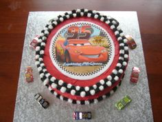 Lightning McQueen cake .... very simple design with edible image and chocolate foil wrapped cars, racing flag design around the top and bottom of the cake really make it stand out.