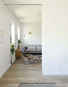 Tiny Streamlined Home Fit for a Family // Dwell Takeshi Nii's Ny chair is paired with a Reese sofa and cherry Grove nightstand from Room & Board in the living room. Small Space Living, Small Spaces, Living Spaces, Minimalist Apartment, Minimalist Living, House Tweaking, Light Hardwood Floors, Apartment Renovation, Family Room Design