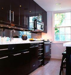 IKEA Kitchen - Glossy Black cupboards, top cupboards black smoked glass & grey benchtops & stainless steel splashback panel.