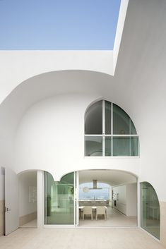 """Dramatic arches characterize this enigmatic California beach house that's elevated six feet above the sand to guard from major storms. Called the Vault House, it was designed by architecture firm Johnston Marklee. As principal Mark Lee explains: """"The envelope was so strict that the design process was more subtractive than additive; we carved away a solid mass to create the rooms. We were reluctant to broadcast the content right away, preferring to mask the complexity and reveal it a little…"""